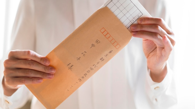 Close-up com as mãos segurando um envelope