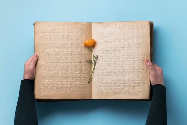 Close-up com mãos segurando um livro antigo