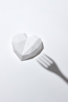 Close up composição de gesso branco coração branco e sombras de garfo