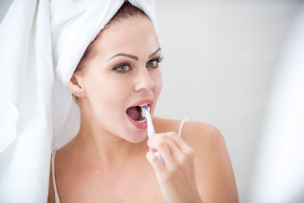 Close-up, concentrado, mulher, escovar, dentes