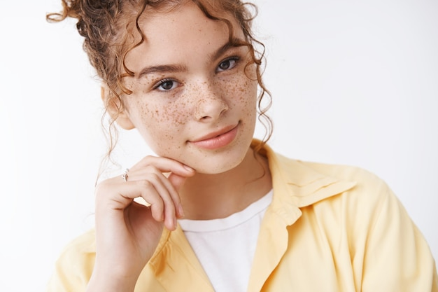 Close-up concurso feminino jovem 20 anos estudante universitária ruiva sardas bochechas sorrindo suavemente tocar a bochecha inclinando a cabeça expressando sensualidade, flertando em pé fundo branco