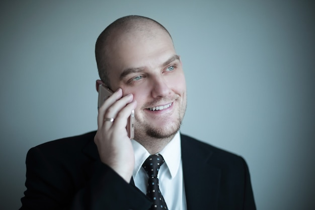 Close up.confident empresário em um empate ouve o interlocutor ao telefone.
