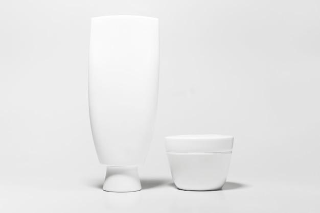 Close-up, conjunto de frasco cosmético e tubo com maquete isolado no fundo branco do estúdio.
