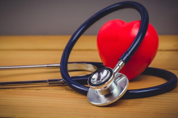Close-up coração vermelho e estetoscópio na mesa de madeira velha