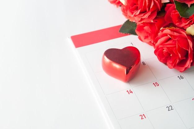 Close-up coração vermelho no calendário com rosa vermelha, conceito dos namorados
