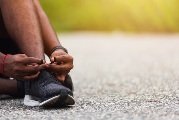 Close-up corredor esportivo homem negro sentado no cadarço experimentando tênis de corrida se preparando para correr