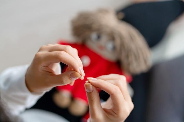 Close up costurando boneca