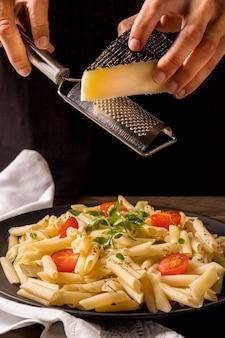 Close-up cozinheiro ralar queijo