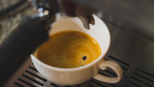 Close up crema coffee shot uma máquina de café expresso derramando no copo da caneca de café dose única e dupla do barista no café da cafeteria.
