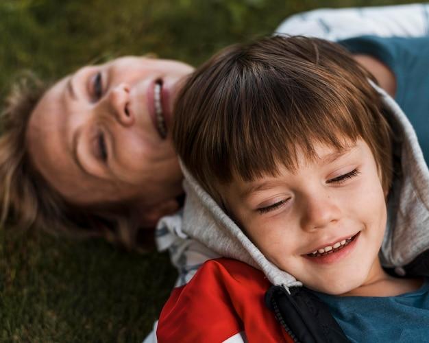 Close-up criança feliz e mulher na grama
