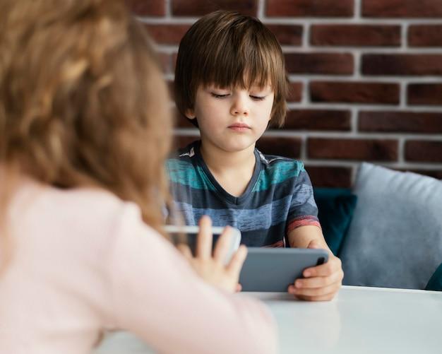 Close-up crianças com tablet e telefone