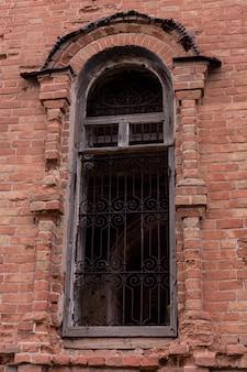 Close-up da abertura da janela na parede de tijolo destruída.