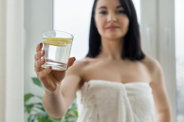 Close-up da água de vidro com limão à disposição da jovem mulher que está em casa perto da janela.