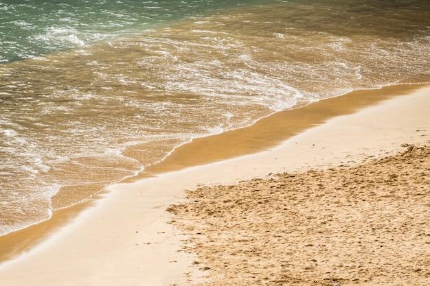 Close-up da água do mar, tocando a areia na costa