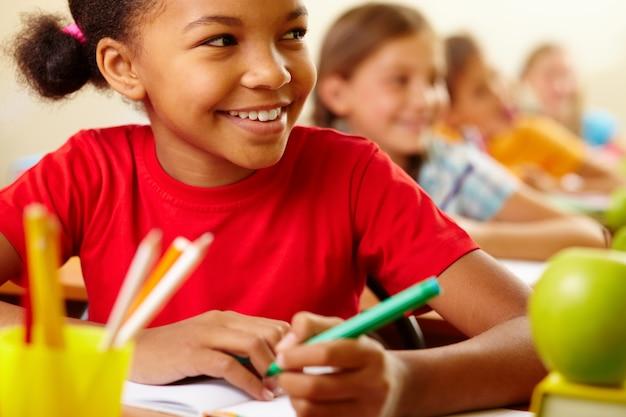 Close-up da alegre aluno com t-shirt vermelho