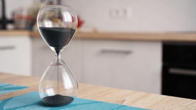 Close up da ampulheta em uma mesa de madeira branca com cozinha de desfocagem. conceito de tempo para cozinhar.