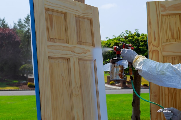Close-up da arma de pulverizador com as portas de madeira da pintura do mestre da pintura da pintura.