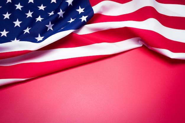 Close up da bandeira americana no fundo vermelho.