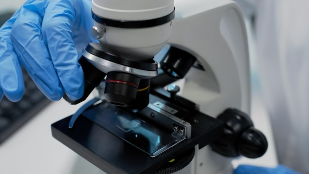 Close-up da bandeja de vidro microscópico no instrumento óptico