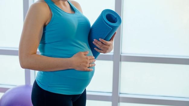 Close-up da barriga de uma mulher grávida com um tapete esportivo.