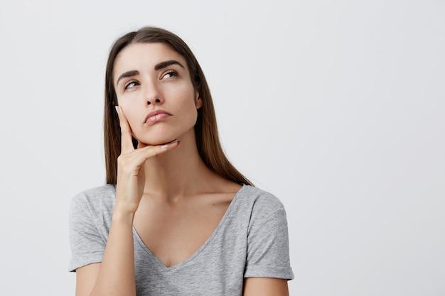 Close-up da bela encantadora jovem aluna caucasiana com cabelos longos escuros na elegante camiseta lisa, segurando o dedo perto do rosto, olhando de lado com expressão pensativa e relaxada