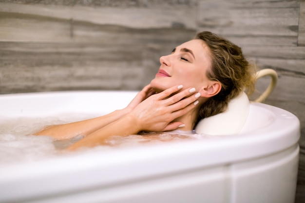 Close-up da bela jovem relaxante no banho termal em um centro de beleza, tocando o rosto, sorrindo