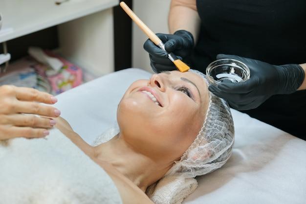 Close-up da bela mulher madura, deitado no procedimento no salão spa