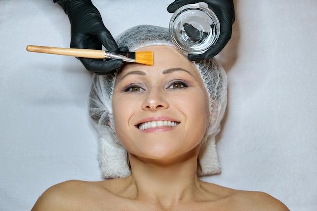 Close-up da bela mulher madura feliz sorridente, deitado no procedimento no salão spa