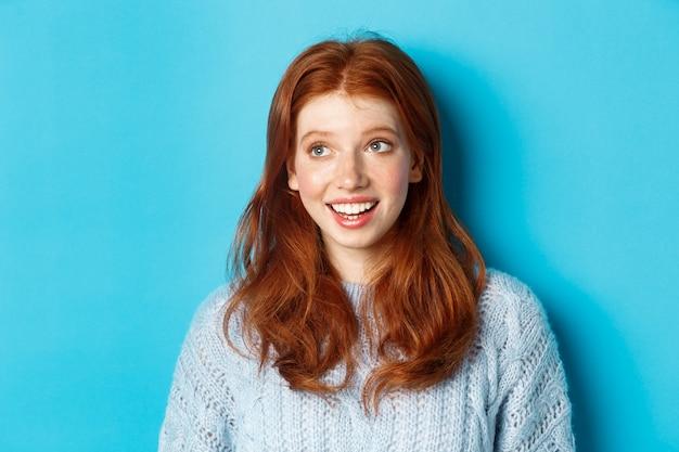 Close-up da bela ruiva de suéter, olhando para o logotipo da promo do canto superior esquerdo e sorrindo, em pé sobre um fundo azul.