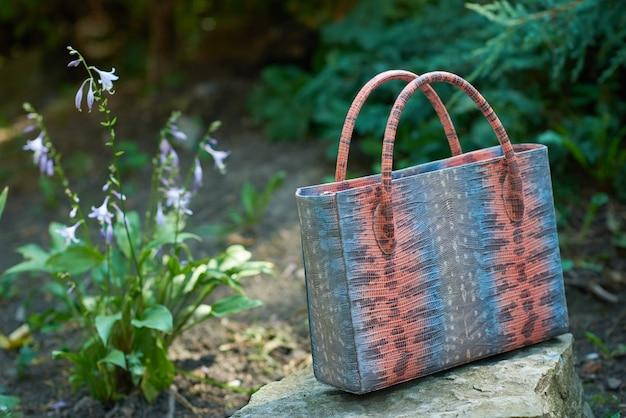 Close-up da bolsa da mulher elegante com imitação de pele de cobra fica na rocha perto de flores no parque. uma bolsa foi confeccionada nas cores azul, rosa e cinza. também possui alças confortáveis.