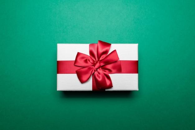 Close-up da caixa de presente branca com laço de fita vermelha na cor verde.
