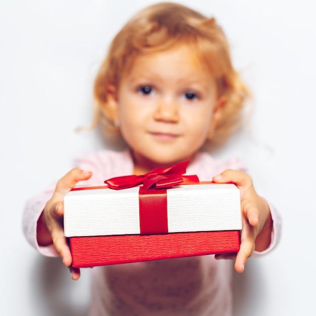 Close-up da caixa de presente com laço de fita vermelha nas mãos de menina de crianças.