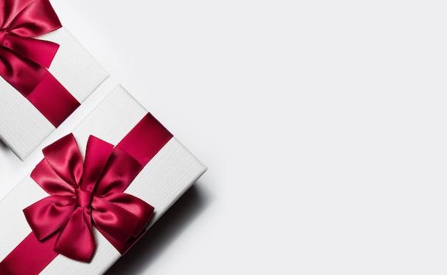 Close-up da caixa de presente com laço vermelho em branco com espaço de cópia.