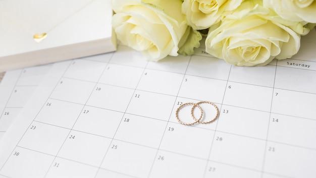 Close-up da caixa de presente; rosas e anéis de casamento no calendário