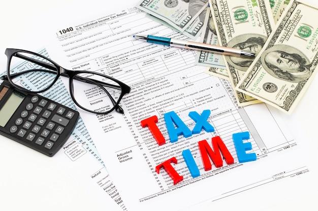 Close-up da calculadora, documentos e alfabeto de madeira com a palavra tempo de imposto sobre a mesa.