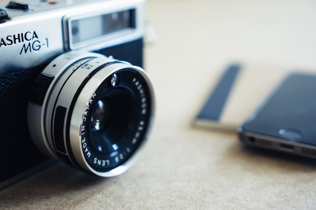 Close-up da câmera do vintage com fundo do smartphone turva