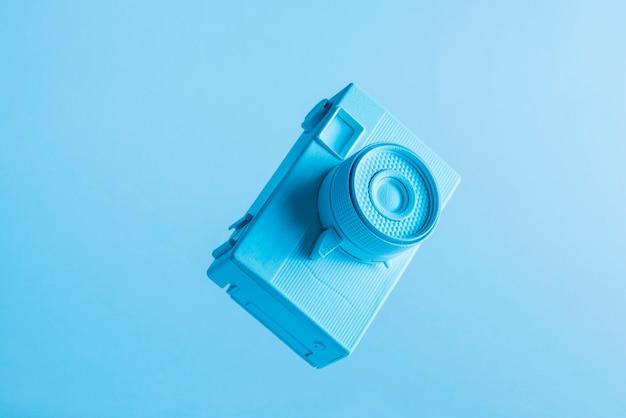 Close-up da câmera pintada no ar contra o pano de fundo azul