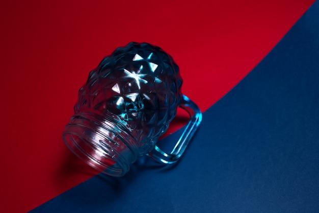 Close-up da caneca de vidro para suco em superfície escura de cor vermelha e azul
