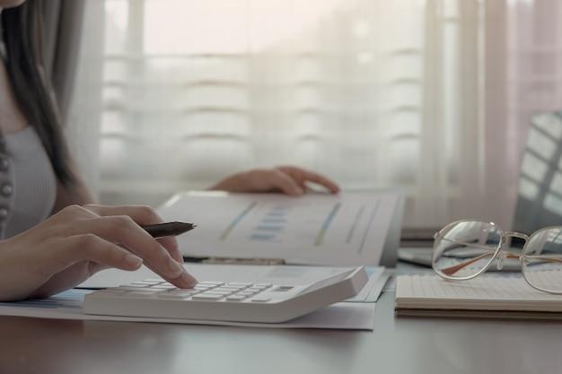 Close-up da caneta de exploração de mão de mulher ou contador trabalhando na calculadora para calcular dados de negócios