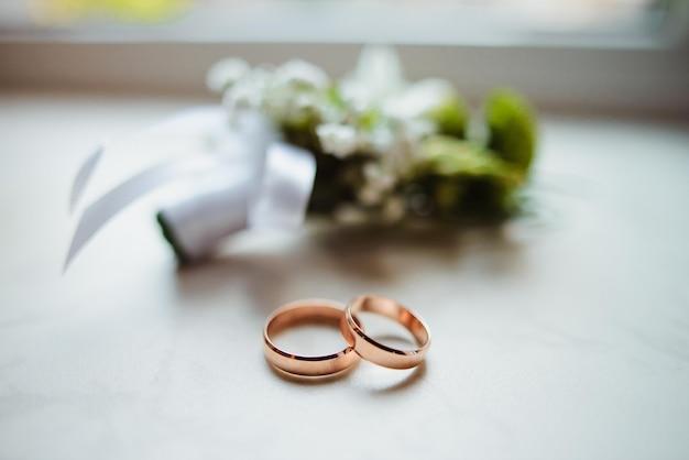 Close up da casa de botão e alianças de casamento