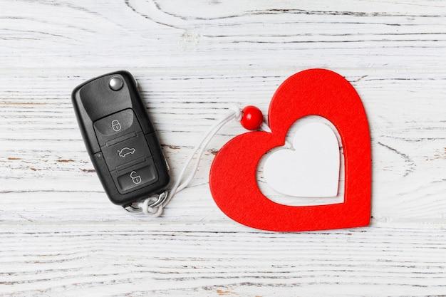 Close-up da chave do carro e coração de brinquedo de madeira