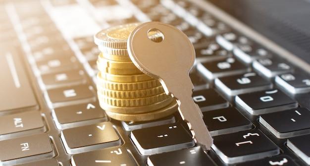 Close-up da chave e pilha de moedas no teclado preto. conceito de seguro