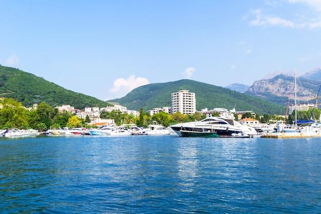 Close-up da cidade de budva de um iate, no fundo uma cordilheira com vegetação. viaje ao longo da costa de montenegro.