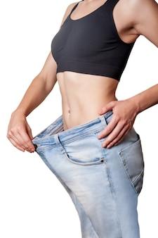 Close-up da cintura fina de jovem em jeans grandes, mostrando a perda de peso bem sucedida, isolada no fundo branco, o conceito de dieta.