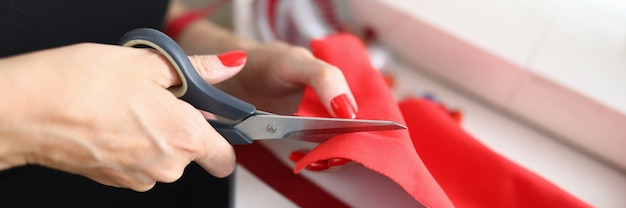 Close-up da costureira qualificada cortando um pano vermelho com uma tesoura.