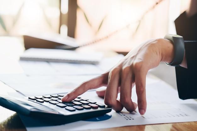 Close-up da empresária. mãos, segurando, telefone, e, calculadora, ligado, escritório, tabela trabalhando
