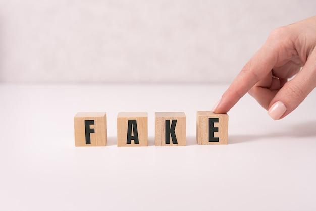 Close-up da empresária segurar cubos com a palavra falso