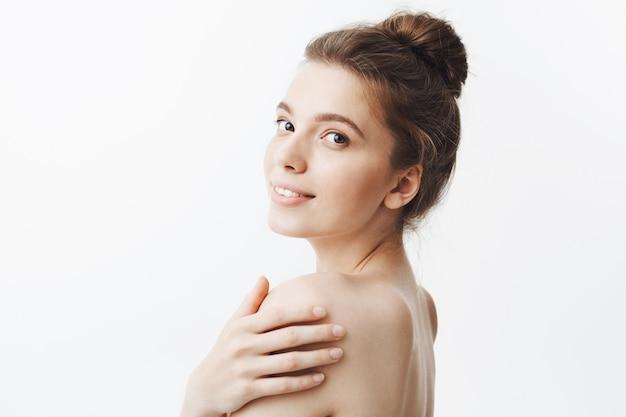 Close-up da encantadora garota atraente jovem estudante com cabelos escuros na coque penteado e corpo nu, sorrindo suavemente com expressão calma e feliz rosto, tocando o ombro com a mão