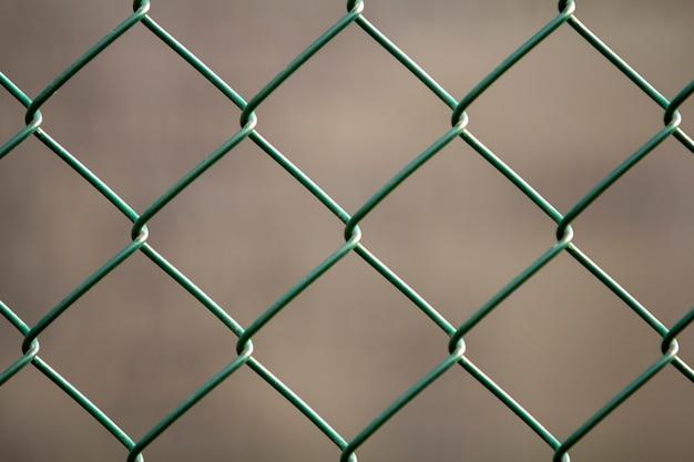 Close-up da éon preto geométrico simples pintado isolado da cerca do elo de corrente do fio de metal do ferro - obscuridade - fundo vermelho. conceito de vedação, proteção e compartimento.