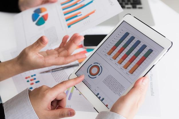 Close-up da equipe do negócio que usa a tabuleta digital com d financeira